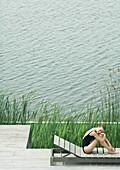 Woman sitting on lounge chair next to lake, hugging knees, smiling
