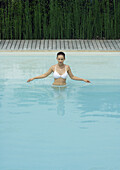 Woman standing in pool with arms out, looking down