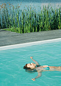 Woman floating on back in pool, waist up