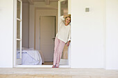 Mature woman in pajamas leaning against wall