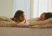 Couple lying in bed talking to each other