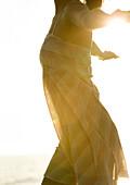 Woman wearing light dress in sun, cropped