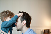 Toddler boy playing with father's hair