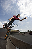 A BMX rider balancing on the edge of a sports ramp