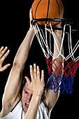 A basketball player trying to make a basket, studio shot