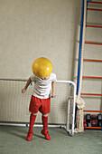 A young boy jumping to head butt a soccer ball away from a goal