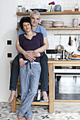 An affectionate smiling mixed age couple in their kitchen