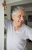 A cheerful senior man standing in a doorway