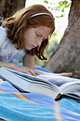 Girl lying down reading book in park