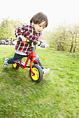 A young boy running on a balance bicycle