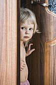 Girl standing by open door