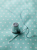 A threaded needle and thimble on top of polka dotted fabric