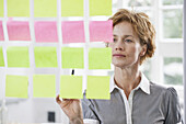 A businesswoman considering rows of adhesive notes on glass