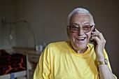 A cheerful senior man living in a nursing home, using a mobile phone