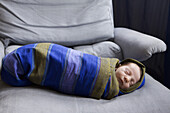 A newborn baby swaddled in a striped blanket