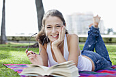 Happy girl in park lying down with book