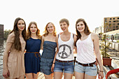 Five cheerful young female friends standing a row, Spree River, Berlin, Germany