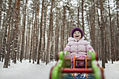 A young cheerful girl on a piece of playground equipment in winter
