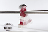A foosball figurine kicking a soccer ball, blurred motion