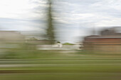 A village in blurred motion viewed from a moving train