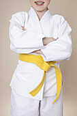 A smiling girl with arms crossed wearing martial arts uniform with yellow belt