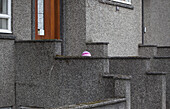 View of the knitted hat of a child in front of a building