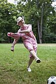 Senior woman kicks football n the park