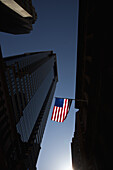 The American flag shown between skyscrapers with a backdrop of a clear blue sky