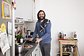 Smiling man looking away while preparing food in domestic kitchen