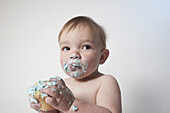 Cute baby boy with messy mouth looking away while holding cupcake against white background