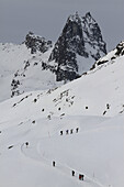 People hiking up a snowy mountain footpath