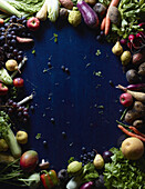 Directly above shot of fresh vegetables and fruits forming circle on blue table