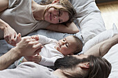 Affectionate parents looking at baby girl while relaxing on mattress