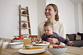 Happy woman looking away while sitting with baby girl at home