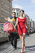 Happy mid adult woman walking while man carrying groceries on street
