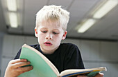 Front view of a small boy attentively reading a book