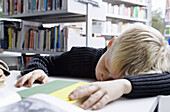 A boy taking a nap on a desk in a library