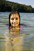 Close-up of young woman swimming in lake