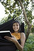 Young woman smiling and reading book in hammock