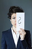Portrait of mid adult woman holding paper with question mark, close-up