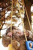 Baby girl sitting on swing, looking away