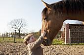 Baby girl stroking horse