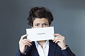 A worried looking woman holding paper with squiggle sign