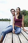Young couple sitting on wooden pier, smiling