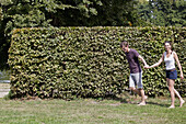 Young couple holding hands and walking by hedge