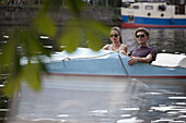 Young couple riding paddle boat on lake