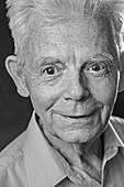 Close-up portrait of smiling senior man over black background