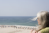 A mature adult woman looking out over a beach