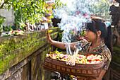 Woman giving offerings, home temple, Ubud, Gianyar, Bali, Indonesia