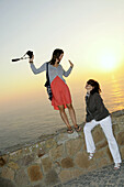 Two women taking photographs at the coast at sunset, Cabo da Roca, West coast near Lisbon, Portugal